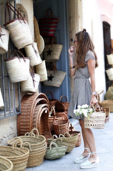 Chica usando un bolso straw handbags con un vestido blanco con negro