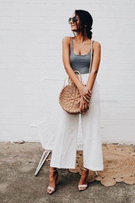 Chica usando un bolso straw handbags con pantalones de campana y blusa cuadrada