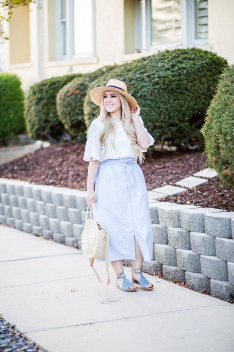 Chica usando un bolso straw handbags con falda y blusa a rayas