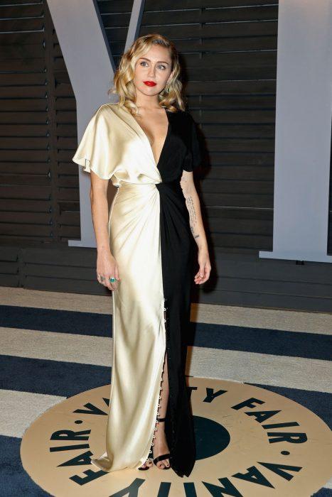 Miley Cyrus usando un vestido dorado y negro