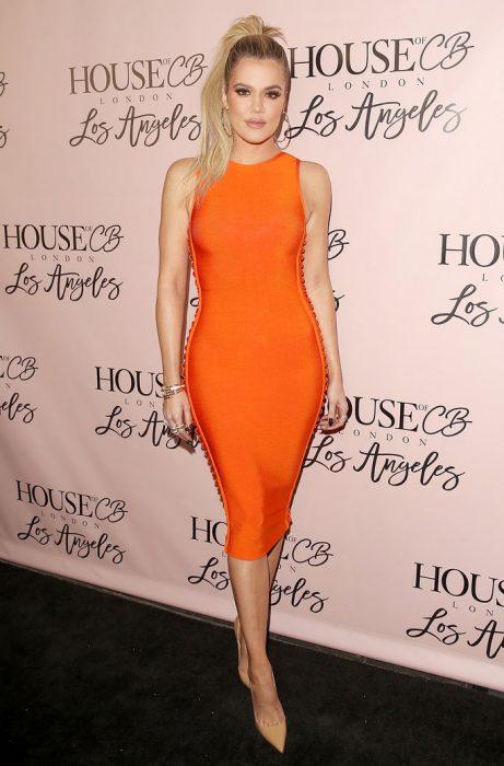 Khloé Kardashian usando un vestido naranja con botones