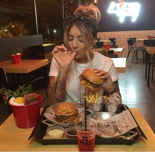 chica comiendo hamburguesas y papas fritas