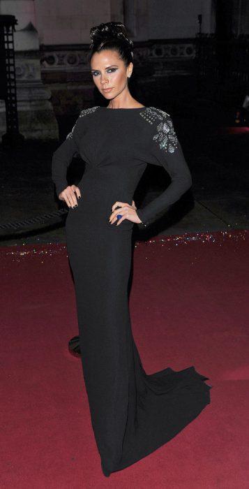 Victoria Beckham usando un vestido negro con hombreras