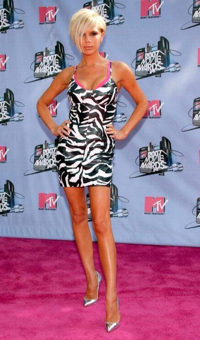 Victoria Beckham con un vestido animal print de rayas y cabello bob rubio