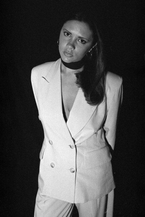 Victoria Beckham usando un traje blanco con una shocker negra
