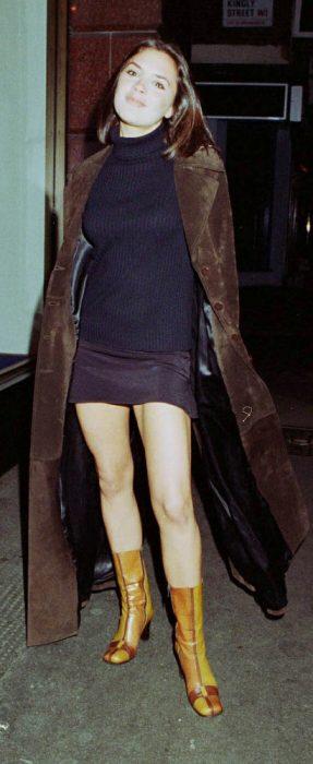 Victoria Beckham usando un saco café falda y botas