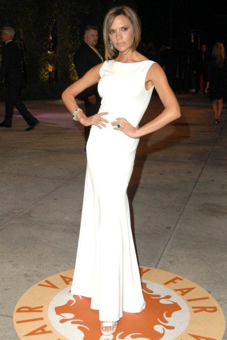 Victoria Beckham usando un vestido blanco en la fiesta de Elton John