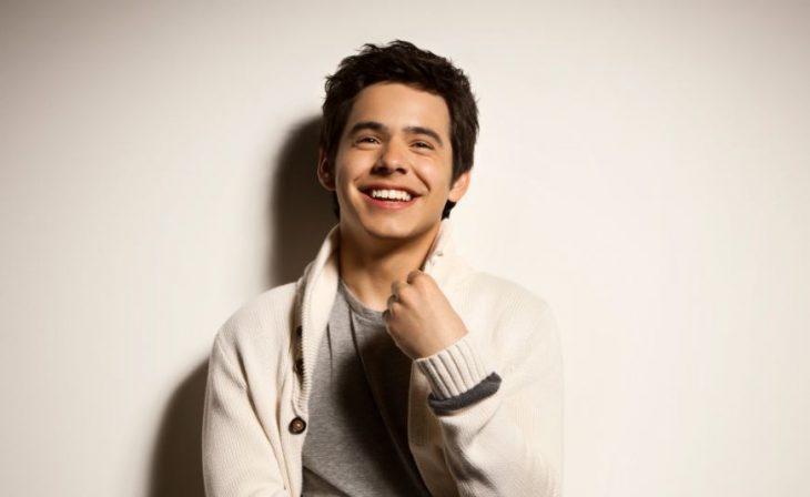 chico sonriendo y usando suéter blanco