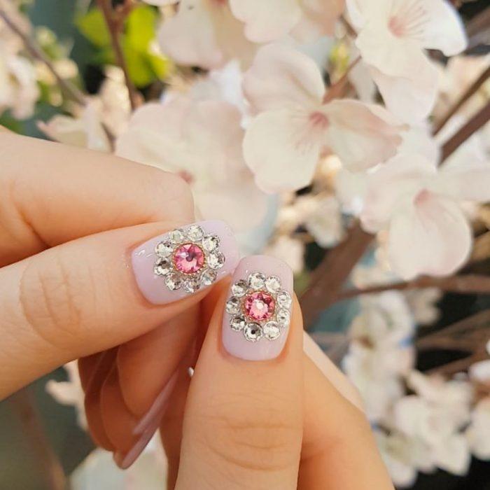 Uñas de vidrio que lucen como diamantes en color lila con piedras rosas