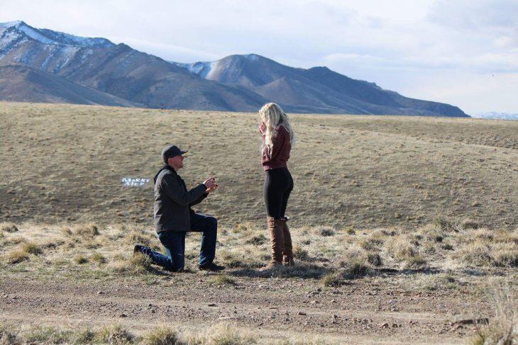 Hombre arrodillado proponiendo matrimonio a una chica