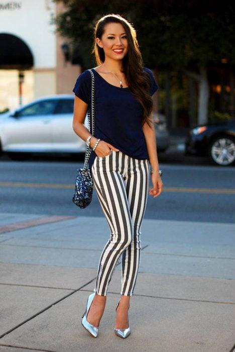 Chica usando zapatillas de color plateado con jeans rayados