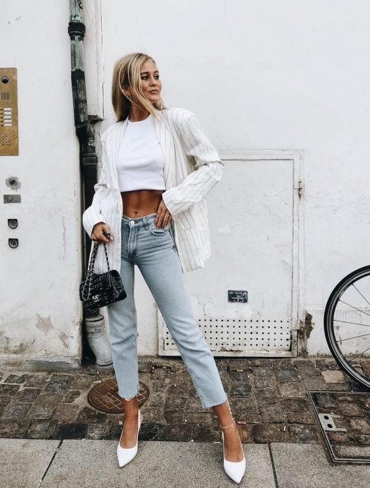 Chica usando blusa blanca con zapatillas blancas y jeans