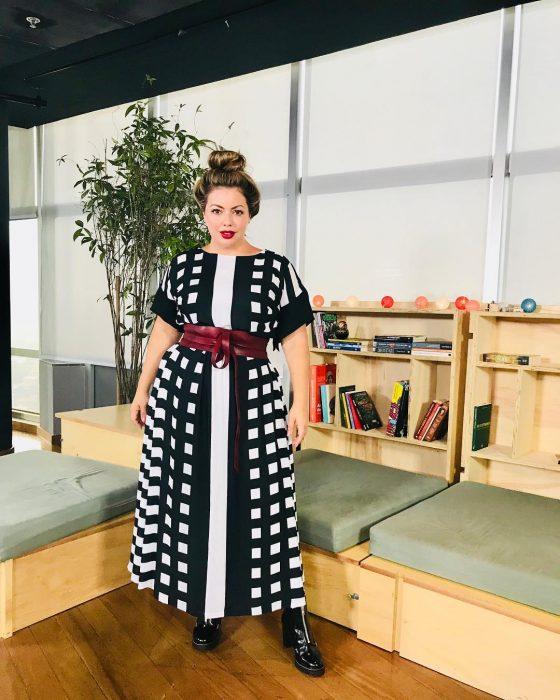 Modelo plus size fluvia Lacerda usando un atuendo de vestido negro con puntos blancos y cinto rojo