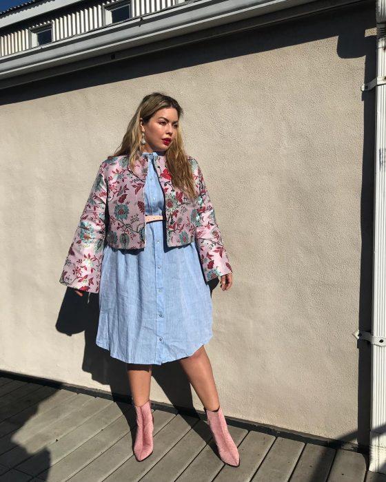 Modelo plus size fluvia Lacerda usando un atuendo de vestido de jean y chamarra rosa
