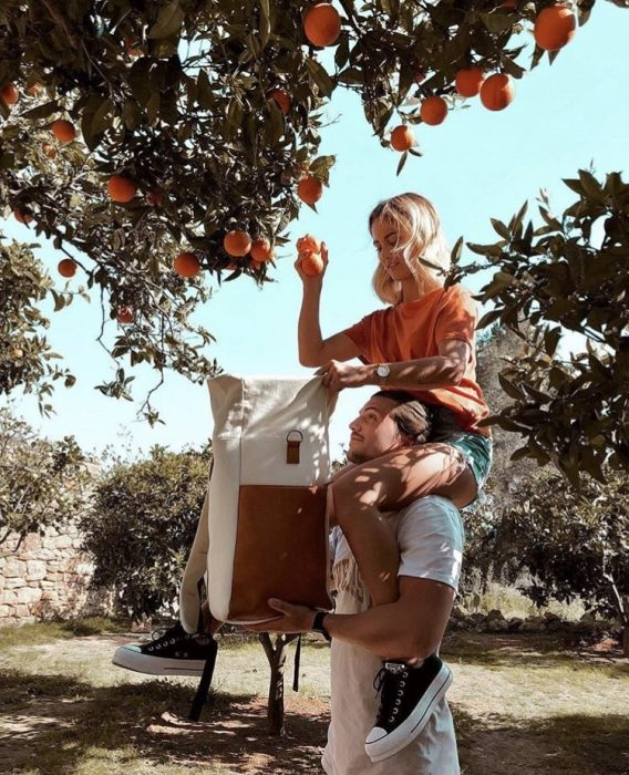pareja de novios recolectando naranjas