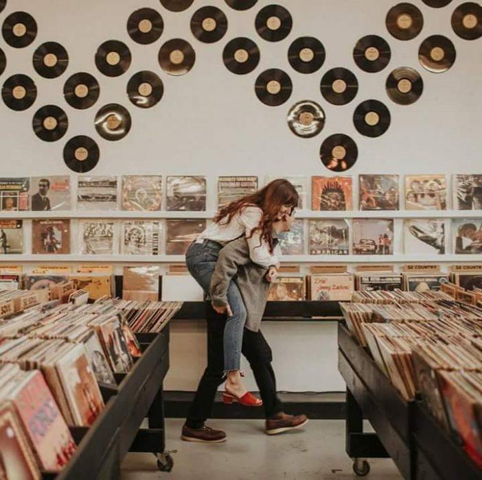 pareja de novios jugando en una tienda de discos