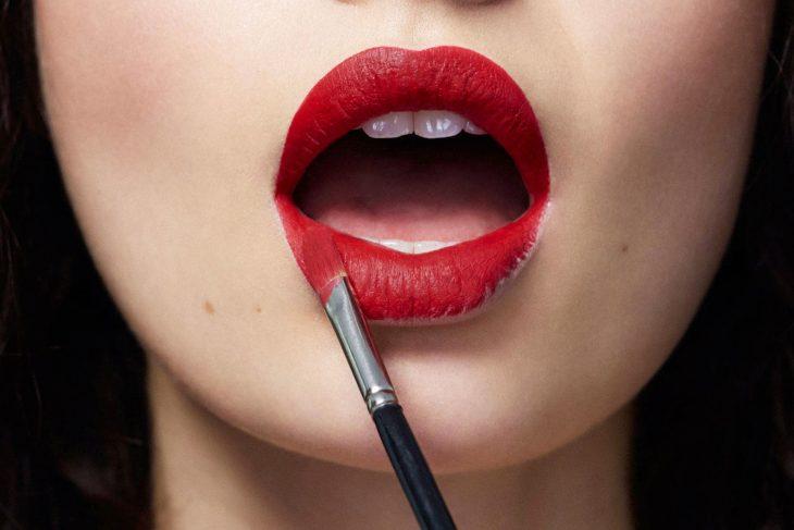 Chica aplicando labial con una brocha