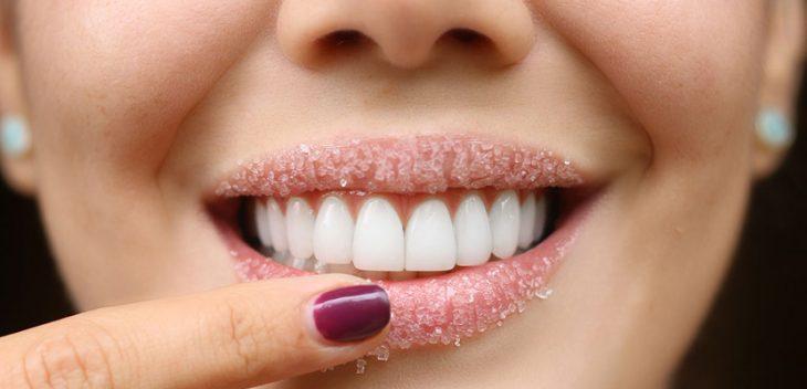 Chica exfoliando sus labios con azúcar