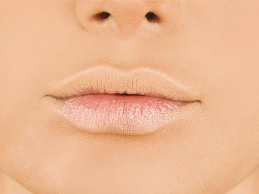 Chica aplicando base y corrector en sus labios