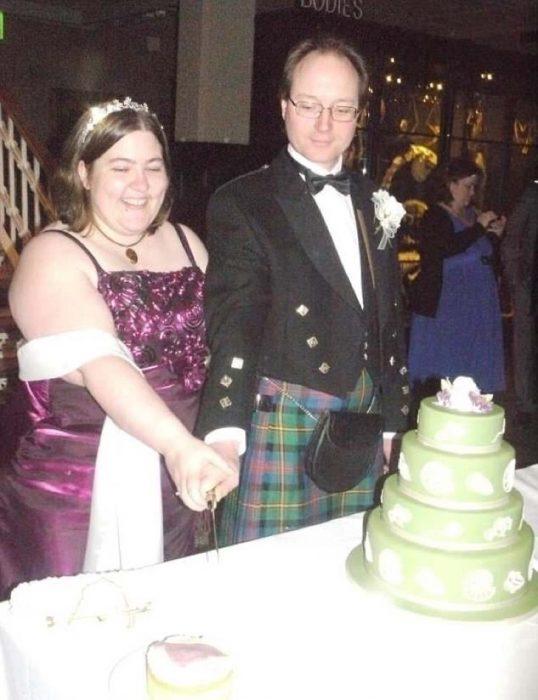 Pareja de novios cortando su pastel de bodas