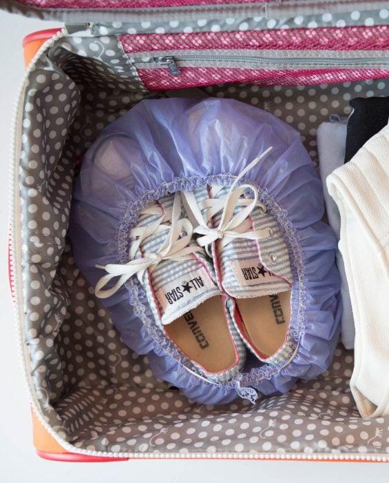 zapatos guardados en gorra de baño dentro de maleta