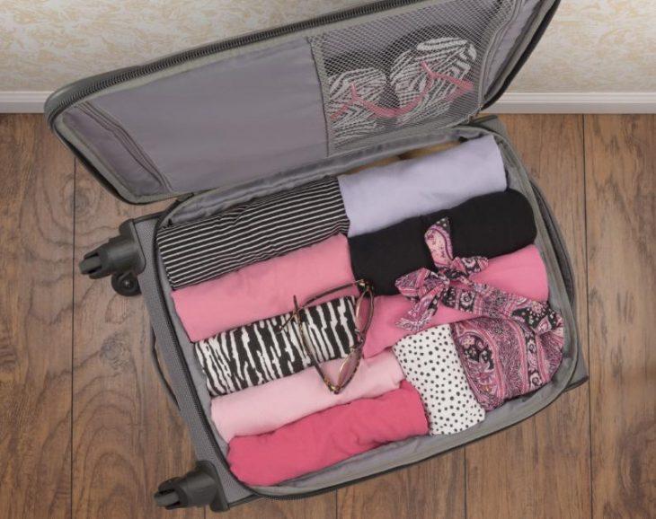maleta con ropa enrollada colores rosas y gris