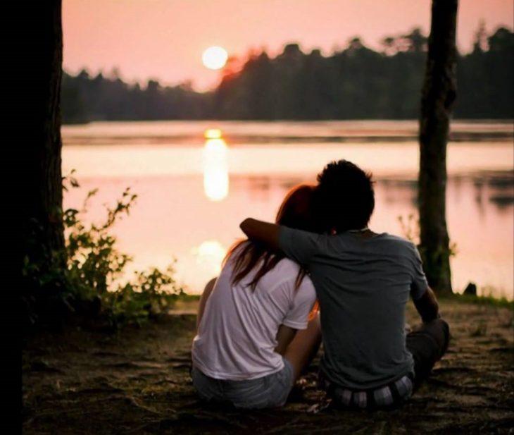Pareja de novios abrazados besándose y viendo un atardecer
