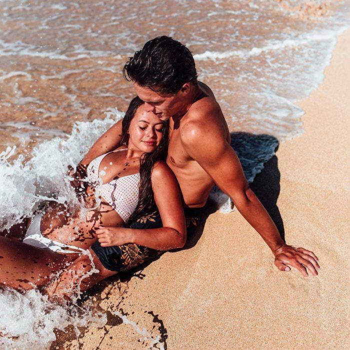 Pareja de novios abrazados besándose mientras están en la playa