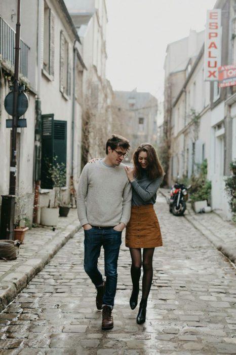 Pareja de novios abrazados mientras van caminando por la calle