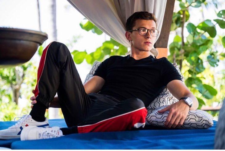 Tom Holland sentado en un sofá azul
