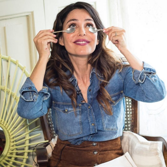 Mujer con cucharas en las bolsas de los ojos