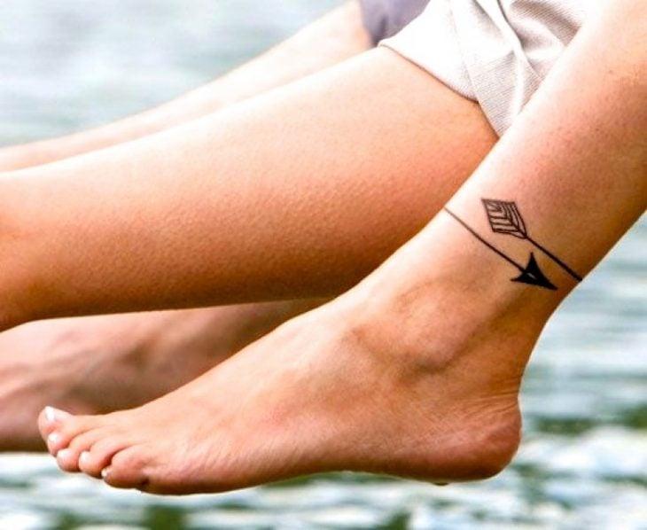 Tatuaje en el tobillo en forma de pulsera con dos flechas