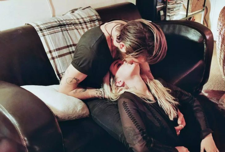 chico besando a su novia en la frete