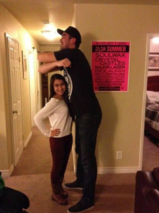 mujer bajita y hombre alto intentando abrazarla