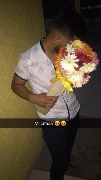 Chico sosteniendo un ramo de flores para sorprender a su novia el día de su cumpleaños
