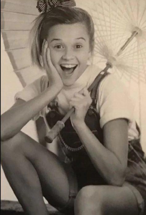 Reese Witherspoon sujetando una sombrilla cuando era niña