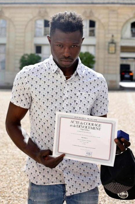Hombre que salvó a un niño sosteniendo un certificado de nacionalidad