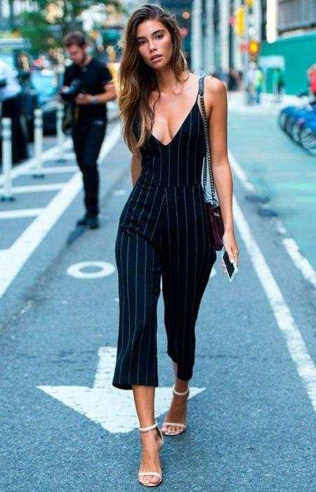 Chica usando un jumpsuit de color negro con líneas