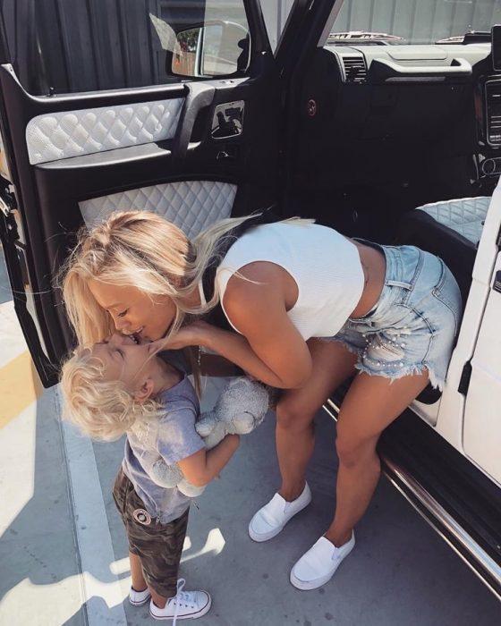 chica besando a su hija en la frente