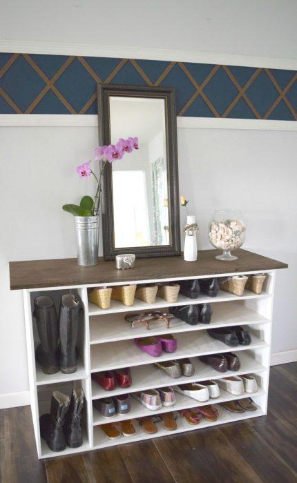 Zpatos acomodados bajo un estante de madera