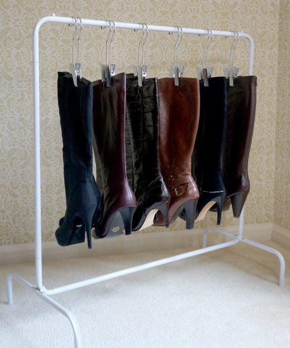 Botas colgadas con ganchos en un toallero