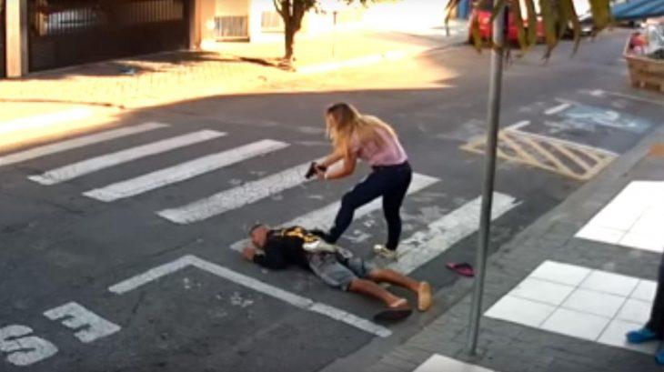 Mujer sometiendo con una arma a un asaltante frente a un grupo de mujeres