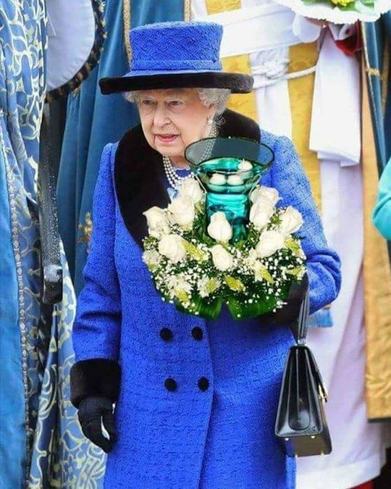 Reina Isabel sosteniendo un adorno de mesa