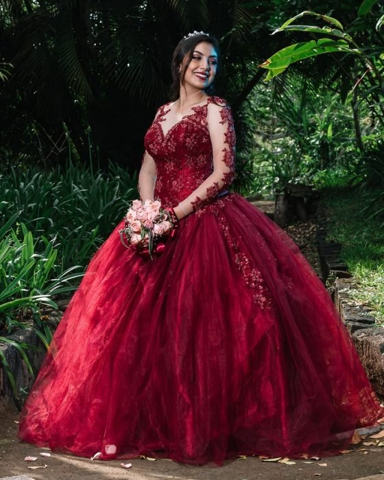 Quinceañera usando un vestido rojo con mangas