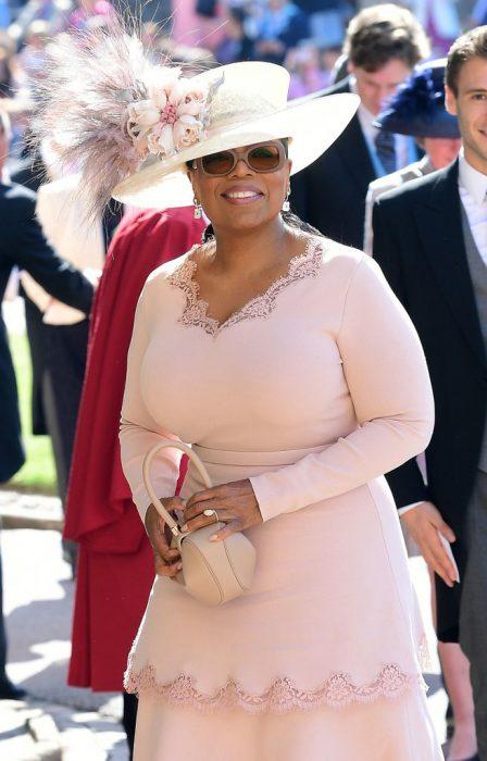 Oprah Winfrey usando un sombrero rosa para la boda real