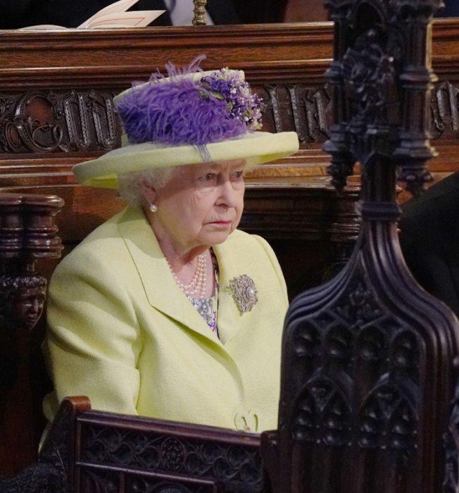 Reina Isabel ll usando un sombrero verde con toques morados en la boda real