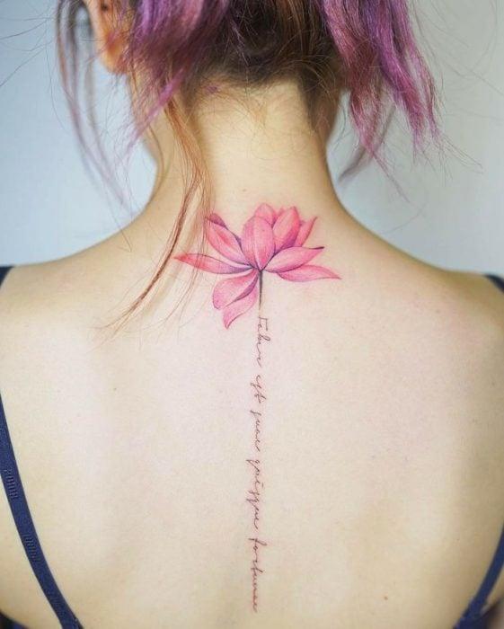 Chica conun tatuaje de espina dorsal con letras y una flor