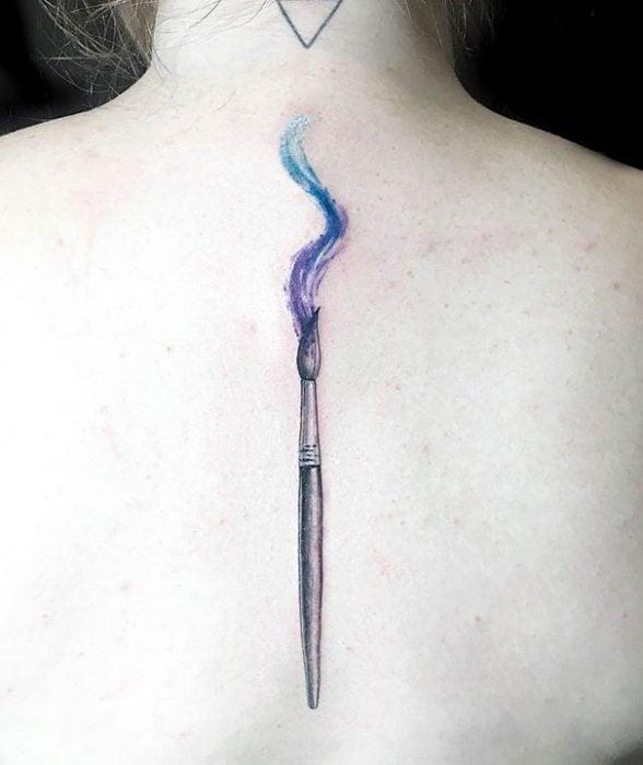 Tatuaje en la espina dorsal con diseño de un pincel