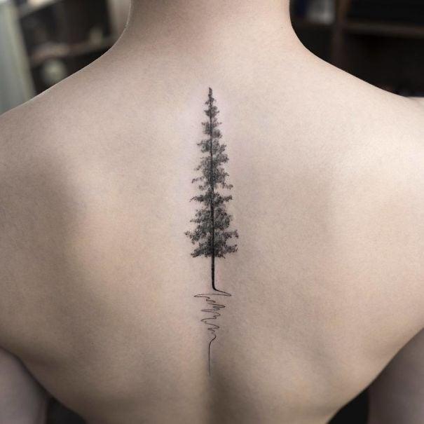 Tatuaje en la espina dorsal con diseño de un pino en medio del bosque