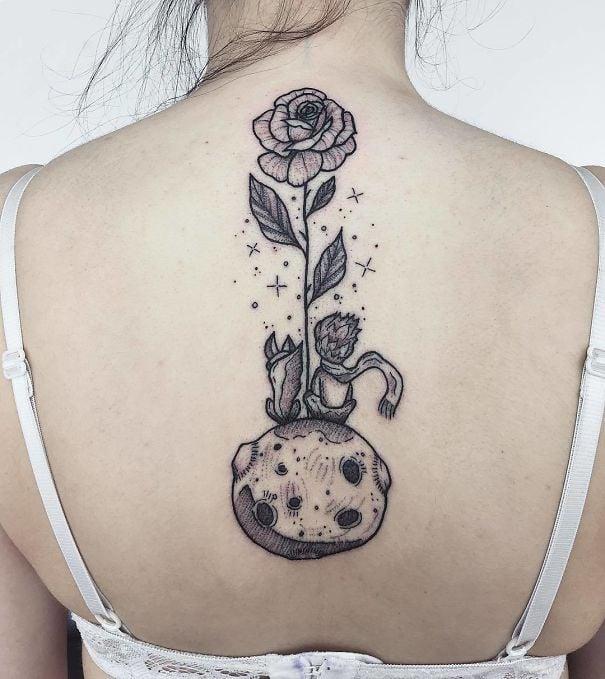 Tatuaje en la espina dorsal con diseño de el principito y una rosa